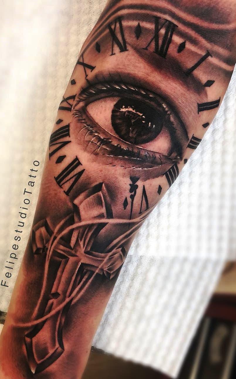 tatuagem-de-cruz-olho-e-relogio-no-antebraço